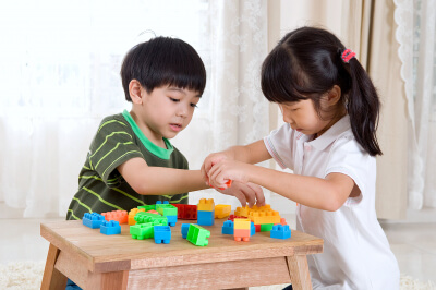 kids piling up building blocks